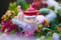 Mentira do gato do brinquedo propensa no gelo das flores foto de stock royalty free