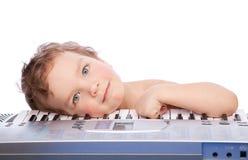 Mentira do rapaz pequeno no teclado de piano Foto de Stock Royalty Free