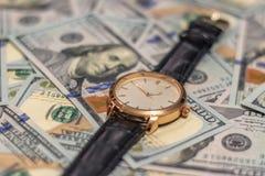 Mentira do relógio de ouro do pulso nas contas do dinheiro de 100 dólares Foco macio fotografia de stock royalty free