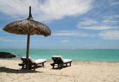 Mentira dois de madeira na praia em Maurícia Foto de Stock Royalty Free