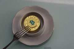 Mentira dourada do bitcoin no copo branco em pires com forquilha de prata foto de stock
