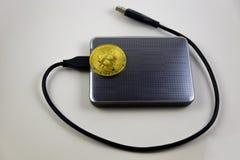 Mentira dourada do bitcoin no disco rígido Fotos de Stock Royalty Free