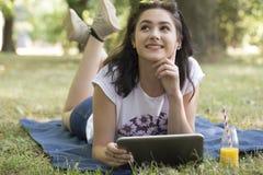 Mentira en la hierba y sostener una tableta Foto de archivo libre de regalías