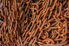 Mentira enredada oxidada de las cadenas en el puerto Fondo Corrosión del metal imagenes de archivo