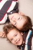 Mentira feliz de dos hermanos en el sofá Imagen de archivo libre de regalías