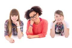 Mentira feliz de tres adolescentes aislada en blanco Imagenes de archivo