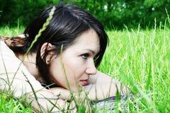 Mentira femenina joven en la hierba Imagen de archivo libre de regalías