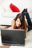 Mentira femenina joven en suelo usando la computadora portátil. Imagen de archivo