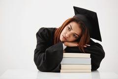 Mentira graduada del africano trastornado en los libros que piensan sentarse sobre el fondo blanco Copie el espacio Foto de archivo