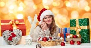 Mentira hermosa de la chica joven en el sombrero con las cajas de regalo - concepto de santa del día de fiesta Foto de archivo