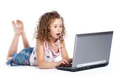 Mentira hermosa de la muchacha sorprendida cerca de la computadora portátil Imagen de archivo