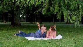 Mentira hermosa de los pares de Retty en la manta blanca puesta en hierba verde y charla linda debajo de follaje grueso metrajes