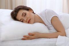 Mentira hermosa el dormir de la mujer joven en cama y relajación por la mañana Un día soleado comienza es la época de ir para un  foto de archivo libre de regalías