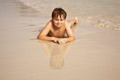 Mentira iy del muchacho en la playa Imagen de archivo libre de regalías