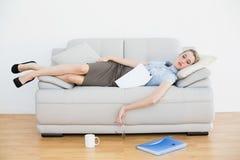 Mentira joven agotada el dormir de la empresaria en su sofá Imagen de archivo