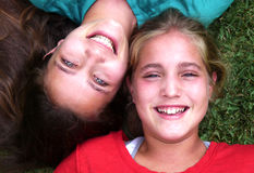 Mentira joven de dos hermanas en hierba Fotografía de archivo