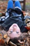 Mentira joven del adolescente al revés en una cama de hojas Imagen de archivo