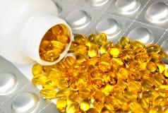 Mentira líquida amarela das cápsulas perto de uma garrafa. Ainda-vida Foto de Stock Royalty Free