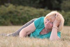 Mentira mayor de la mujer exterior y sonrisa Foto de archivo libre de regalías
