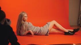 Mentira modelo de la muchacha rubia abajo presentando para el fotógrafo - luz profesional en estudio Foto de archivo libre de regalías