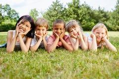 Mentira multicultural de los niños en hierba imágenes de archivo libres de regalías