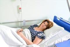 Mentira paciente femenina en cama en sala de hospital Imagen de archivo