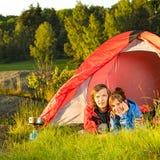Mentira que acampa de los pares jovenes en tienda Imagen de archivo libre de regalías