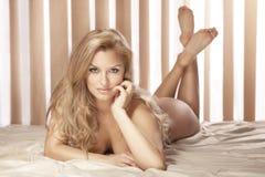 Mentira rubia atractiva de la mujer descubierta en la cama, mirando la cámara Fotografía de archivo