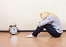 Mentira rubia emocional en el piso que lleva a cabo los pies del reloj Fotografía de archivo libre de regalías