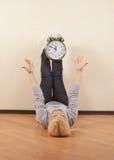 Mentira rubia emocional en el piso que lleva a cabo los pies del reloj Foto de archivo