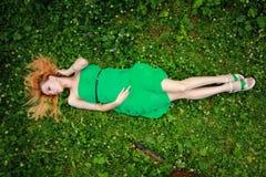 Mentira rubia hermosa en la hierba, mirando abajo, visión superior Imágenes de archivo libres de regalías
