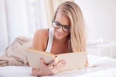 Mentira rubia hermosa joven en una cama y lectura de un libro Fotografía de archivo libre de regalías