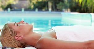 Mentira rubia pacífica en poolside de la tabla del masaje metrajes