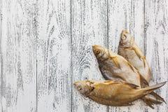 Mentira secada de la brema de tres pescados en una tabla de madera ligera imagenes de archivo
