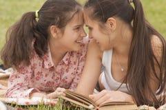 Mentira sonriente de la madre y de la hija al aire libre Foto de archivo