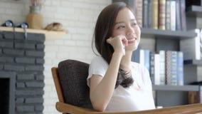 Mentira sonriente de la mujer asiática joven hermosa para relajar sentarse en silla en la sala de estar