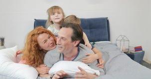 Mentira sonriente feliz de la familia junto en padre en el dormitorio, padres alegres con los niños por mañana metrajes