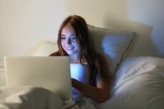 Mentira sonriente hermosa joven de la mujer en manos del control de la cama en el ordenador portátil co Fotos de archivo