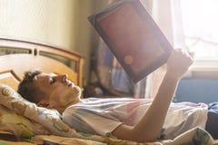 Mentira y el dormir en la cama en casa y leer el libro por la mañana f imagenes de archivo
