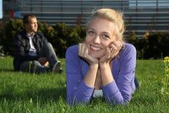 Mentira y hombre de la mujer que se sientan en parque Imagen de archivo