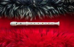 Mentiras da cor do leite da flauta do bloco em um fundo vermelho imagem de stock royalty free