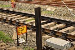 Mentiras das trilhas de estrada de ferro ao lado de um sinal do ponto da estrada de ferro indiana imagem de stock
