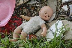 Mentiras de la muñeca abandonadas en una descarga de basura Fotografía de archivo