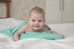Mentiras de riso da crian?a do beb? envolvidas em uma toalha ap?s o banho olhar impertinente do menino positivo alegre da menina  imagens de stock royalty free