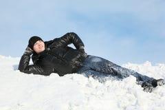 Mentiras del hombre joven en la palma de la ayuda de la nieve fotografía de archivo libre de regalías