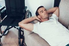 Mentiras do homem perto da cadeira de rodas em Sofa With Closed Eyes fotografia de stock royalty free