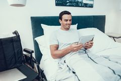 Mentiras inválidas na cama perto da cadeira de rodas e da almofada dos usos foto de stock royalty free