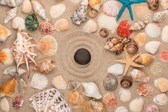 Mentiras pretas da pedra no centro do círculo, do quadro das conchas do mar e das estrelas Imagem de Stock Royalty Free