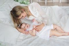 Mentiras y juegos jovenes felices de la madre con su pequeño bebé en una cama Fotos de archivo