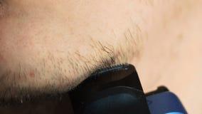 Mento di rasatura dell'uomo con il rasoio elettrico al rallentatore stock footage